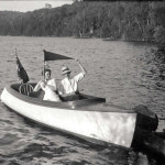William Gorrie is seen here with an unidentified female companion, piloting a launch likely on Lake Kashagawigamog. The Gorrie family enjoyed motor launch outings on many of the local lakes with friends.